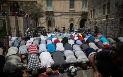 Muslim worshippers pray at an entrance to the Temple Mount at the Lion's Gate in Jerusalem's Old City, July 25, 2017. Muslim worshippers still refused to pray on the Temple Mount following the government's decision remove the metal detectors and instead place more security cameras on the compound. (Hadas Parush/Flash90)