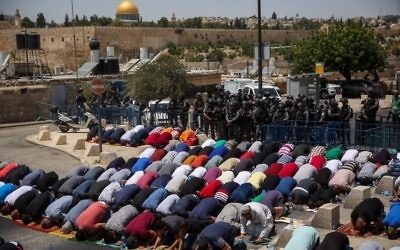 Muslim Palestinians pray as Israeli policemen stand guard during Friday prayers in the East Jerusalem neighborhood of Ras el Amud, outside the Old City, July 28, 2017 (Hadas Parush/Flash90)
