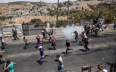 Palestinians run as Israeli police fire tear gas after Friday prayers in the East Jerusalem neighborhood of Wadi al-Joz, July 28, 2017 (Miriam Alster/Flash90)