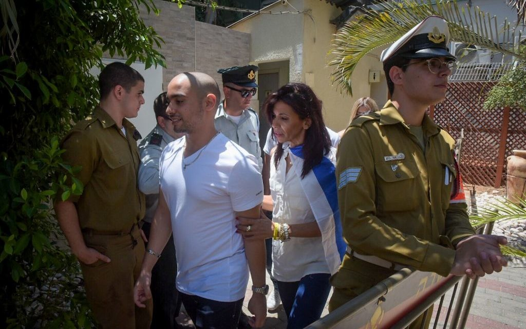 Former IDF soldier Elor Azaria, center, accompanied by his mother, Oshrat, arrive at the Kirya military base in Tel Aviv, July 30, 2017. (Avshalom Sasoni/Flash90)