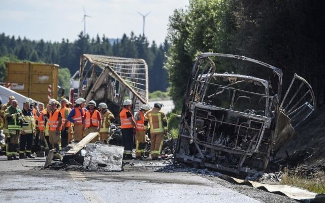 Firefighters work on the wreckage of a burnt-out bus at the place of an accident on the motorway A9 near Muenchberg, Germany, July 3, 2017. (Matthias Balk/dpa via AP)