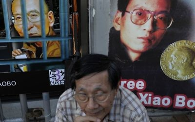 A protester sits in front of pictures of jailed Chinese Nobel Peace laureate Liu Xiaobo during a demonstration outside the Chinese liaison office in Hong Kong, Thursday, July 13, 2017. (AP Photo/Vincent Yu)
