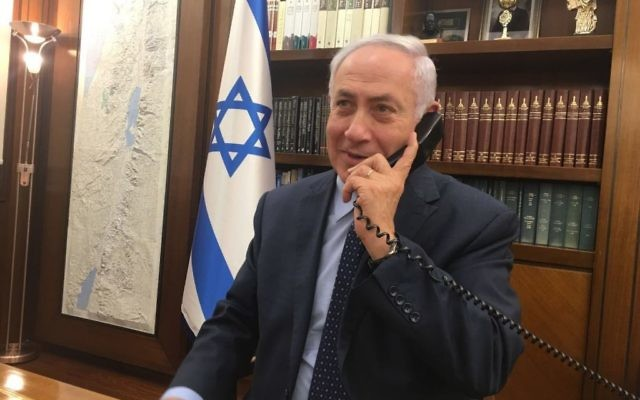 Prime Minister Benjamin Netanyahu speaks on the phone with Israel's ambassador to Jordan, Einat Schlein, and the security official who was stabbed and shot two Jordanians, on their return to Israel, July 24, 2017. (courtesy)