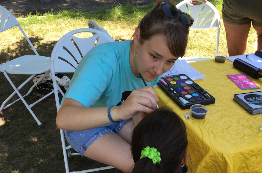 Jhena Vigrass says her work with Repair the World, such as volunteering to do face painting at a Crown Heights festival, has helped her become more involved in the Jewish community. (Courtesy of Vigrass/via JTA)