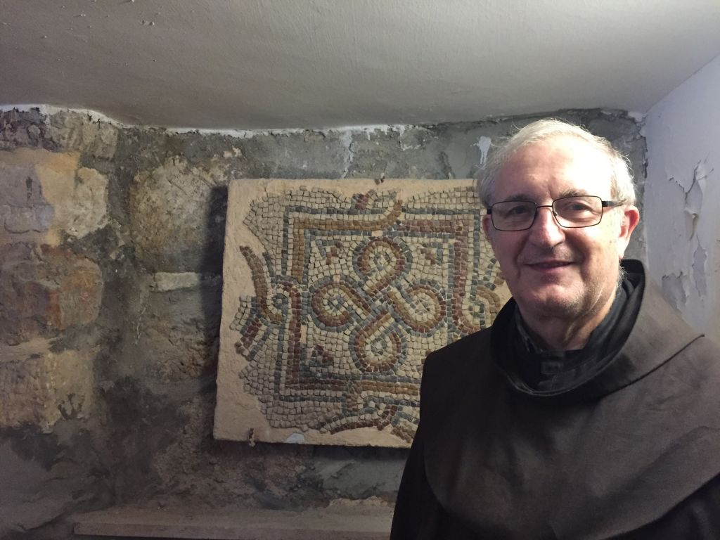 Father Eugenio Alliata stands next to a Byzantine-period mosaic in the Terra Sancta Museum in Jerusalem's Old City. (Amanda Borschel-Dan/Times of Israel)