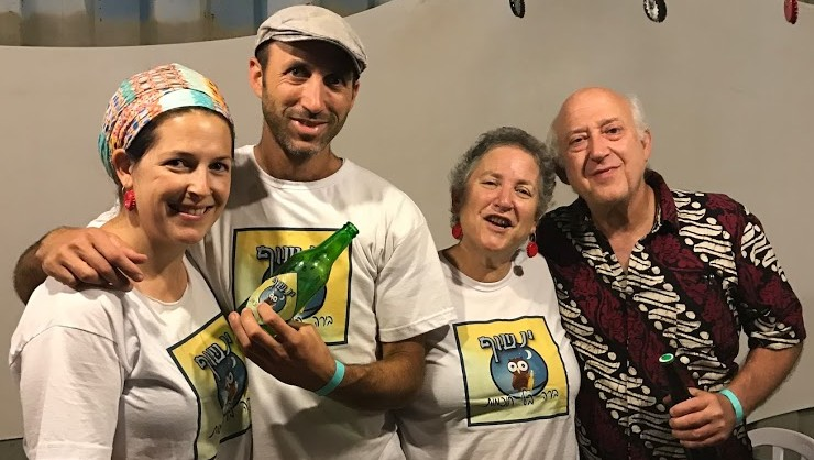 Members of the Baum family selling their Yanshuf (Owl) beer at their booth at the Tekoa Beer Festival on July 6, 2017. (Jacob Magid/Times of Israel)