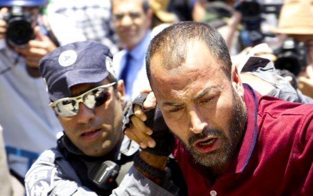A Muslim protester is arrested outside Jerusalem's Old City on July 19, 2017 (Dov Lieber/Times of Israel)