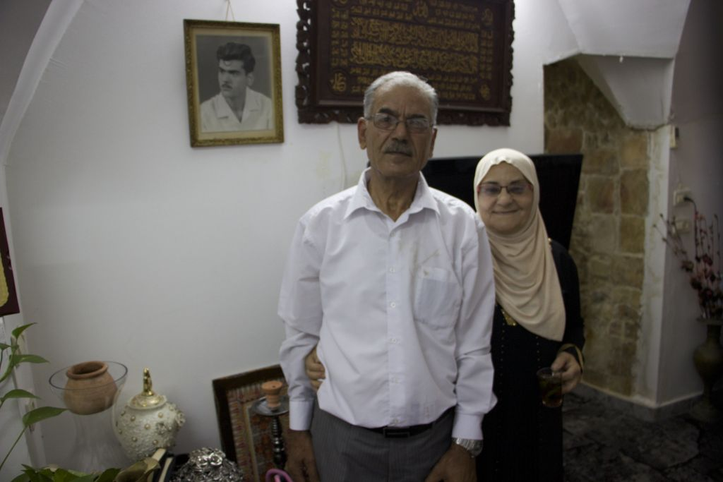 Abid Alfkhawi, 72, stands next to his wife, Umm Jammal, in their home in the Old City of Jerusalem, which is located near the Lions Gate. Above Abid is a picture of him from 1971. (Micah Danney/Times of Israel)