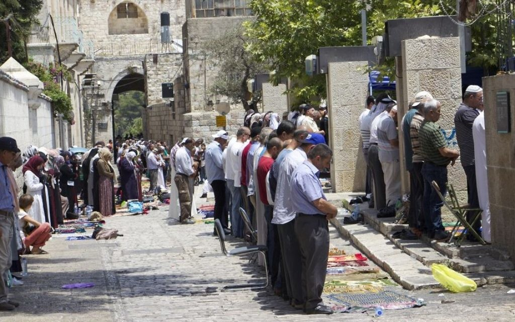 Muslim worshipers pray at the Lions Gate in Jerusalem's Old City on July 21, 2017.  (Dov Lieber/ Times of Israel)