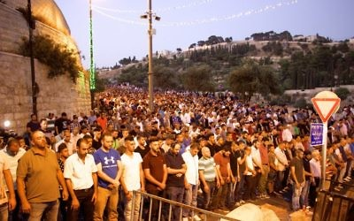 Thousands of Muslim worshipers participate in evening prayers outside the Lions Gate in the Old City of Jerusalem, refusing to enter the Temple Mount enclosure to reach the Al-Aqsa Mosque inside, July 25, 2017. (Dov Lieber /Times of Israel)