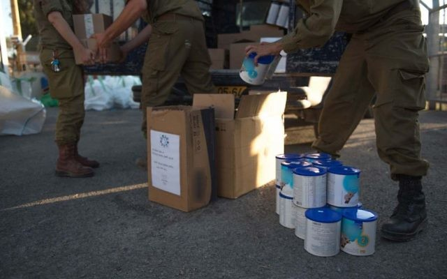 In this undated photo provided on July 19, 2017, IDF soldiers prepare humanitarian aid as part of the army's 'Good Neighbor' program to provide humanitarian aid for Syrian civilians on the Syrian Golan Heights. (IDF spokesperson)