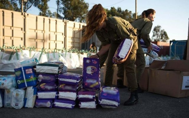 In this undated photo provided on July 19, 2017, IDF soldiers prepare humanitarian aid as part of the army's 'Good Neighbor' program for Syrian civilians on the Syrian Golan Heights. (Israel Defense Forces)