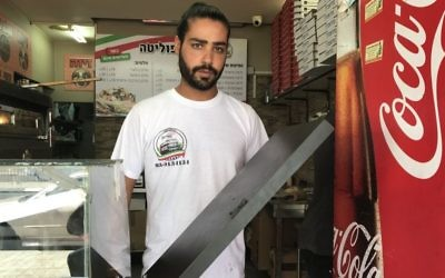 Shlomi Madar holds up the counter-top that separated him from the Palestinian terrorist who tried to stab him in his pizza kiosk in Petah Tikva, July 24, 2017. (Jacob Magid/Times of Israel)