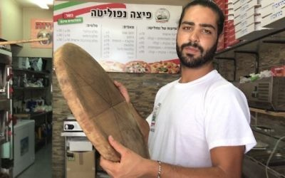 Shlomi Madar with the wooden pizza pie tray similar to the one he used to fend off a Palestinian terrorist who tried to stab him in his pizza kiosk in Petah Tikva, July 24, 2017. (Jacob Magid)