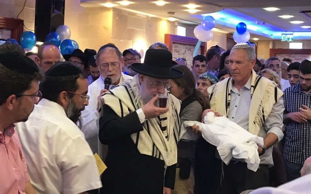 Members of the Salomon family attend the circumcision of their son, Ari, in the central Israel city of Elad, on July 27, 2017. (Jacob Magid/Times of Israel)