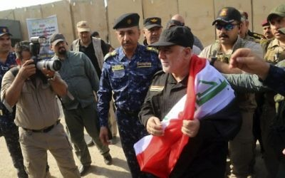 Iraq's Prime Minister Haider al-Abadi, center, holds a national flag upon his arrival to Mosul, Iraq, Sunday, July 9, 2017. Backed by the US-led coalition, Iraq launched the operation to retake Mosul from Islamic State militants in October. (Iraqi Federal Police Press Office via AP)