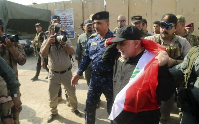 Iraqi Prime Minister Haider al-Abadi, center, holds a national flag upon his arrival to Mosul, Iraq, July 9, 2017. (Iraqi Federal Police Press Office via AP)