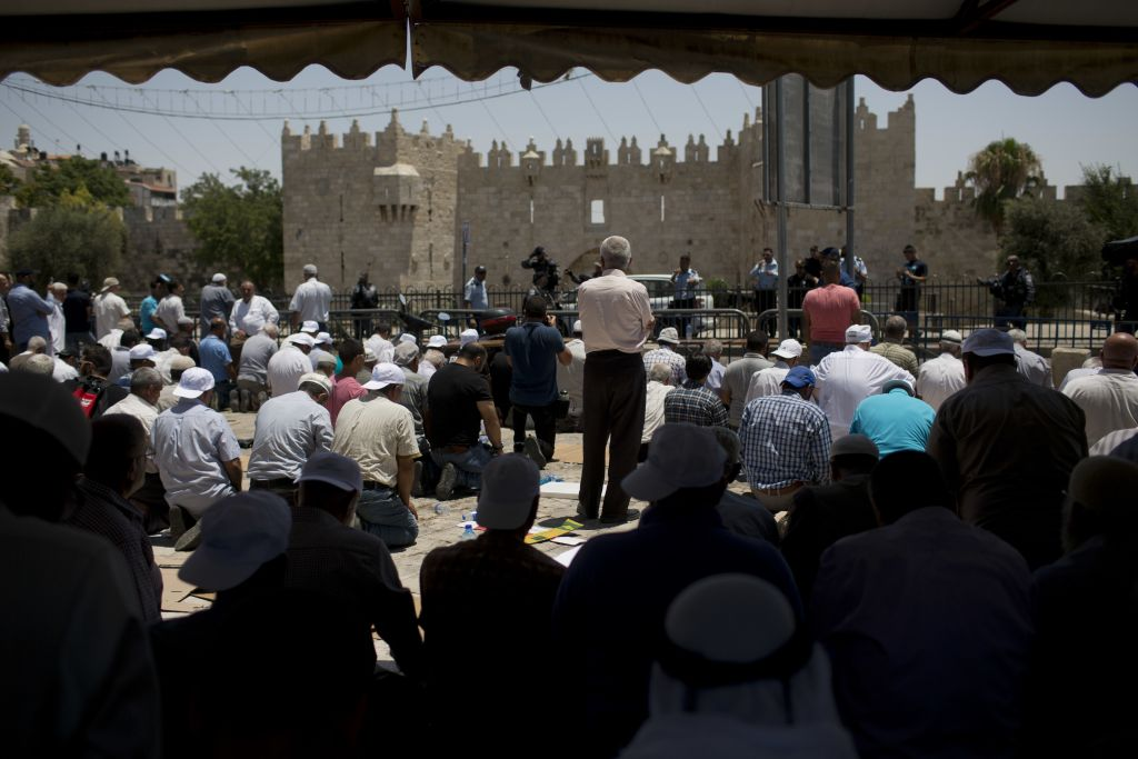 Muslim worshipers gather for Friday prayer outside Jerusalem's Old City, Friday, July 14, 2017. Temple Mount was temporarily closed off after two officers were killed in an attack by three Arab-Israeli gunmen there. (AP Photo/Oded Balilty)