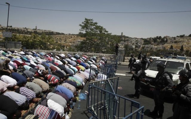 Muslim worshipers prevented from entering the Al-Aqsa Mosque at the Temple Mount pray outside Jerusalem's Old City, Friday, July 14, 2017. (AP Photo/Mahmoud Illean)