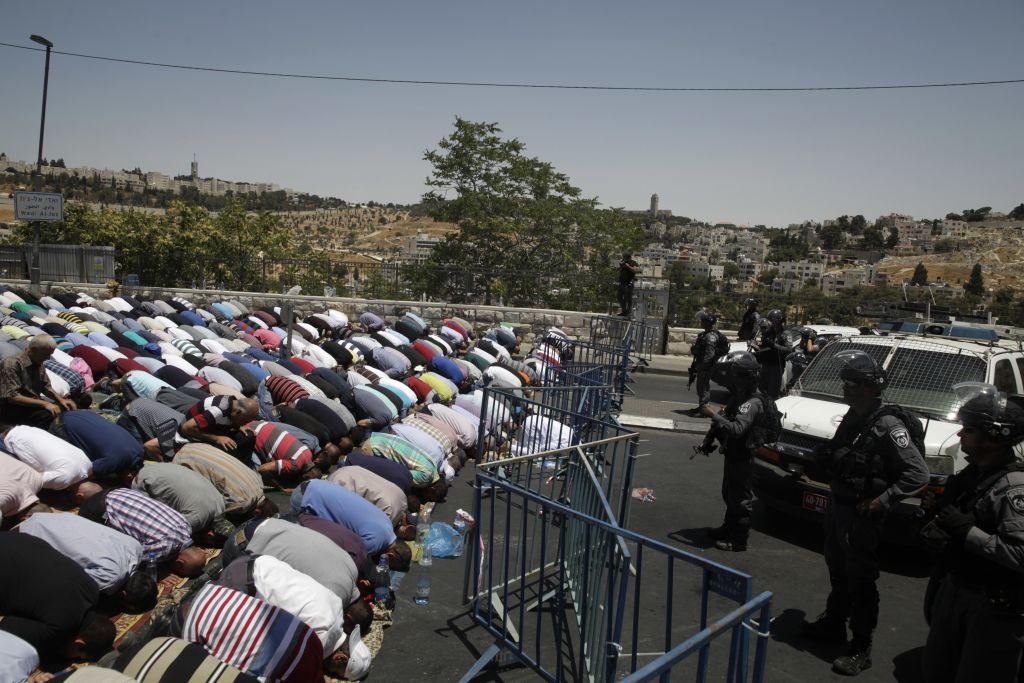 Muslim worshipers prevented from entering the Al-Aqsa Mosque at the Temple Mount pray outside Jerusalem's Old City, Friday, July 14, 2017. Israel's police chief said two officers were killed in an attack by Arab-Israeli assailants near the Temple Mount. (AP Photo/Mahmoud Illean)