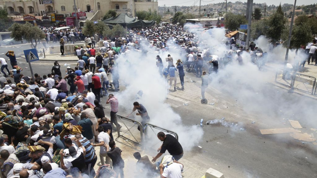 Palestinians run away from tear gas thrown by police officers outside Jerusalem's Old City, Friday, July 21, 2017. (AP Photo/Mahmoud Illean)