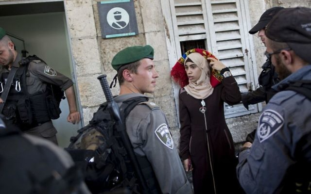 Border Police officers stop a Palestinian woman for a security check as Palestinians gather for prayer at the Lions Gate, following an appeal from clerics for Muslims to pray in the streets instead of the Al-Aqsa Mosque compound on the Temple Mount, in Jerusalem's Old City, Wednesday, July 19, 2017. (AP Photo/Oded Balilty)