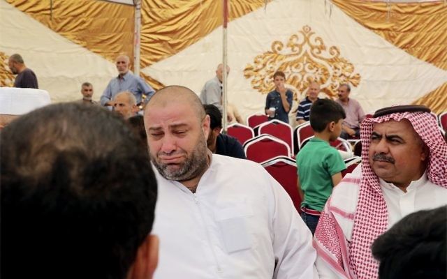 Zakaria al-Jawadah, center left, the father of Mohammed Mohammed al-Jawawdeh, a 17-year-old Jordanian, who was killed on Sunday evening by an Israeli security guard who said he was attacked by him with a screwdriver, cries at a funeral tent in Amman, Jordan, Monday, July 24, 2017.  (AP Photo/Reem Saad)