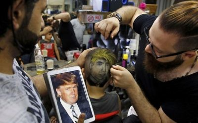 In this Friday, July 14, 2017 photo, Muhannad Khaled Omar, right, prepares an image of US President Donald Trump on the back of a customer's head at his barber shop in Burj al-Barajneh, southern Beirut, Lebanon. (AP Photo/Bilal Hussein)