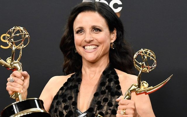 """Julia Louis-Dreyfus shows off the Emmy Awards for best actress in a comedy series and best comedy series for """"Veep"""" at the Primetime Emmy Awards in Los Angeles, Sept. 18, 2016. (Frazer Harrison/Getty Images)"""