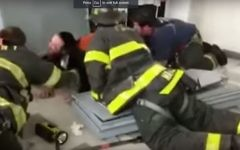 Screen capture from video shows firefighters rescuing an ultra-Orthodox man after he hid inside a safe that toppled on top of him in a yeshiva in Flatbush, New York, July 10, 2017. (YouTube/VINnews)