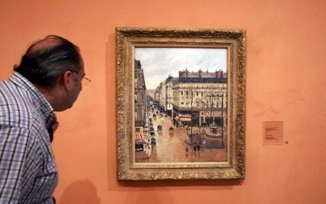 "This May 12, 2005 file photo shows an unidentified visitor viewing the Impressionist painting called ""Rue St.-Honore, Apres-Midi, Effet de Pluie"" painted in 1897 by Camille Pissarro, on display in the Thyssen-Bornemisza Museum in Madrid. (AP/ Mariana Eliano)"