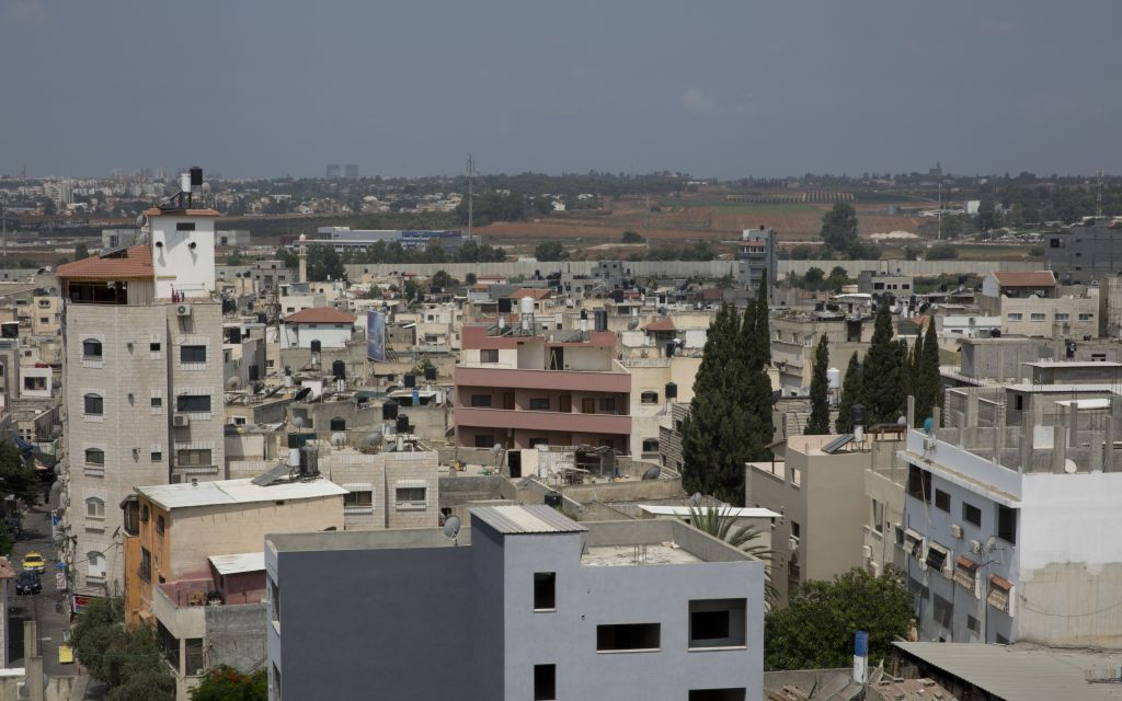 In this photo taken Wednesday, July 5, 2017, a general view shows a crowded Palestinian neighborhood that almost collides with a section of the Israeli security barrier that surrounds the city from three sides, in the most densely populated West Bank city of Qalqilya. (AP Photo/Nasser Nasser)