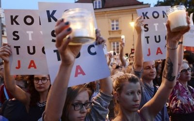 Anti-government protesters raise candles and placards reading 'Constitution,' as they gather in front of the Supreme Court in Warsaw, Poland, Saturday, July 22, 2017 (AP Photo/Alik Keplicz)