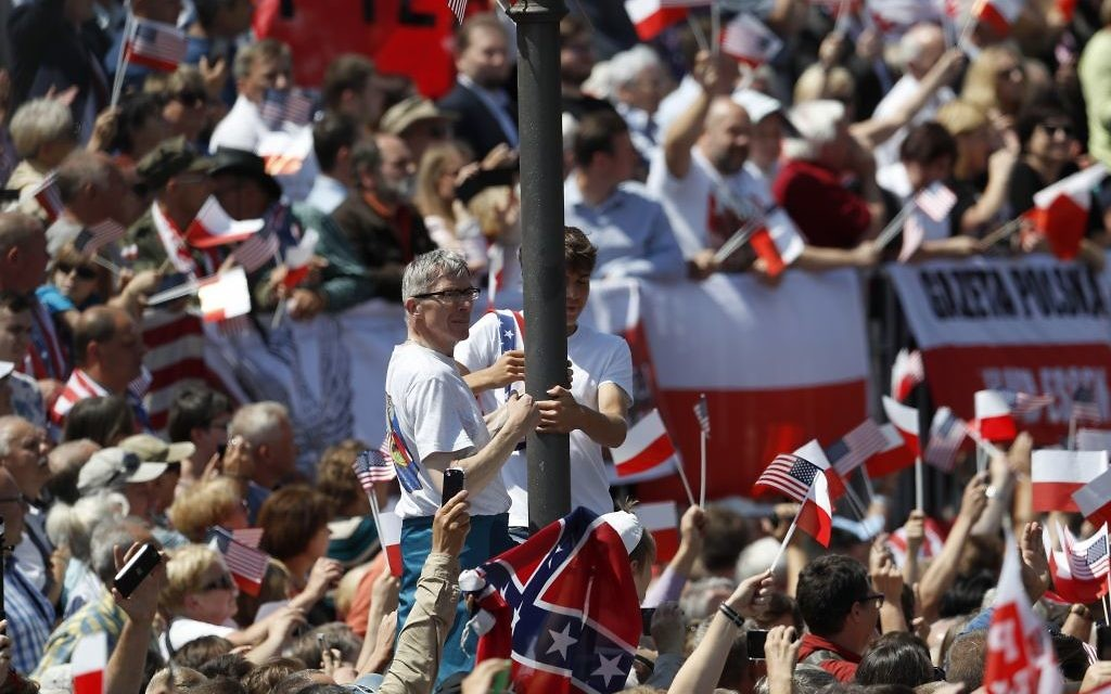 People climb a pole as others wave flags waiting for US President Donald Trump to deliver a speech in the city's Krasinski Square, in Warsaw, Poland, Thursday, July 6, 2017.(AP/Petr David Josek)