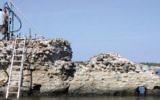A scientist collects concrete samples from the Roman era Portus Cosanus pier in Orbetello, Italy (JP Oleson)
