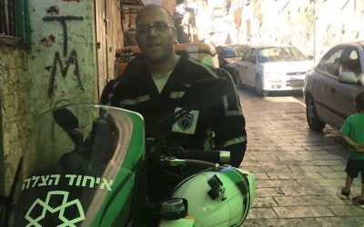 Nedal Sader sitting on his United Hatzalah motor-scooter in the Old City of Jerusalem, July 14, 2017. (Andrew Tobin)