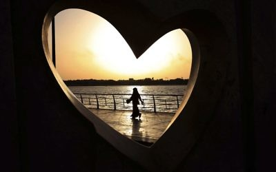 In this May 11, 2014 photo, a Saudi woman is seen through a heart-shaped statue walks along an inlet of the Red Sea in Jiddah, Saudi Arabia. (AP Photo/Hasan Jamali)