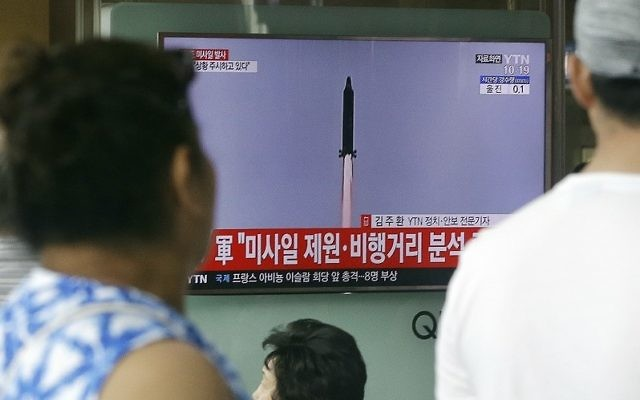 People watch a TV news program showing a file image of a missile being test-launched by North Korea, at the Seoul Railway Station in Seoul, South Korea, Tuesday, July 4, 2017 (AP Photo/Ahn Young-joon)