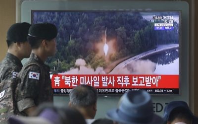 Army soldiers walk by a TV news program showing a file image of a missile being test-launched by North Korea at the Seoul Railway Station in Seoul, South Korea, Tuesday, July 4, 2017 (AP Photo/Ahn Young-joon)