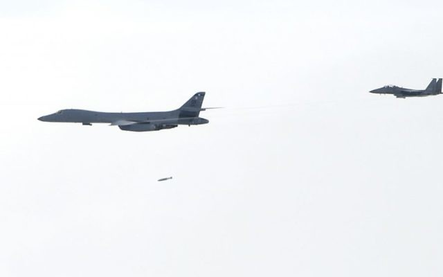 In this photo provided by South Korea Defense Ministry, A U.S. Air Force B-1B Lancer bomber, left, drops a bomb over the Korean Peninsula, South Korea Saturday, July 8, 2017.  (South Korea Defense Ministry via AP)