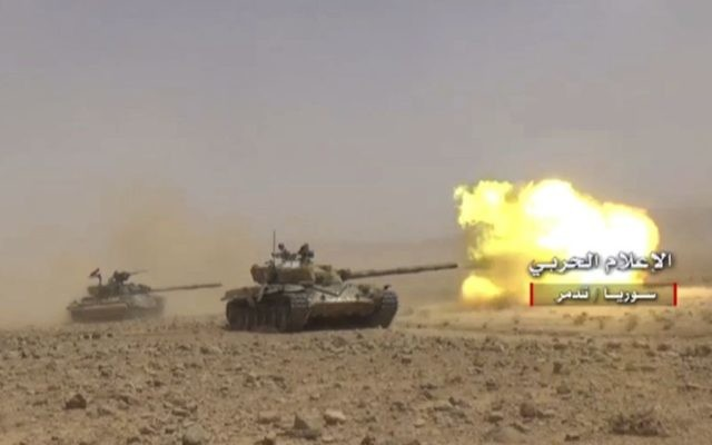 This frame grab from video released on May 24, 2017 and provided by the government-controlled Syrian Central Military Media, shows a Syrian forces tank firing at Islamic States positions in Homs province, Syria (Syrian Central Military Media, via AP)
