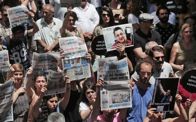In this Tuesday, June 21, 2016 file photo, protesters demonstrate against the jailing of two journalists and an academic, outside the offices of Ozgur Gundem, a pro-Kurdish publication subject to multiple investigations and lawsuits, in Istanbul. (AP Photo/Lefteris Pitarakis, File)