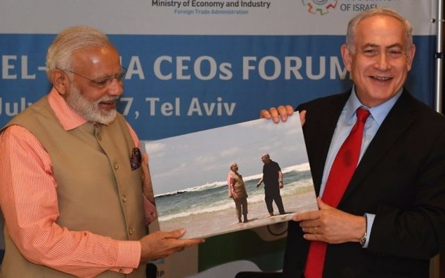 Prime Minister Benjamin Netanyahu gives a picture to his Indian counterpart Narendra Modi of the two leaders' visit to Haifa's Olga Beach on July 6, 2017. (Kobi Gideon/GPO)