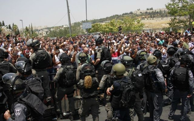 Israeli security forces stand guard in front of Palestinian Muslim worshipers outside Lions Gate , July 21, 2017. (Judah Ari Gross/Times of Israel)