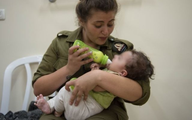 In this undated photo provided on July 19, 2017, an IDF soldier feeds a Syrian baby in Israel as part of the army's humanitarian aid program to assist Syrians impacted by the civil war in their country. (IDF spokesman)