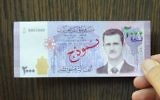 In this photo released by the Syrian official news agency SANA, a man displays a new bank note of 2,000 Syrian Lira, ($3.9) featuring the face of President Bashar Assad, during a press conference for Central Bank Governor Duraid Durgham in Damascus, Syria, July 2, 2017. (SANA via AP)