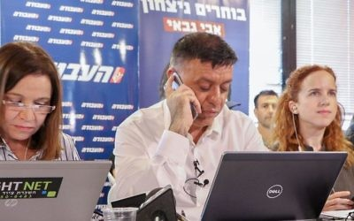 Flanked by former party boss Shelly Yachimovich (left) and Labor lawmaker Stav Shaffir, Avi Gabbay (C), one of two candidates for the Labour Party leadership, phones potential voters ahead of the second round of the party primaries in Tel Aviv, July 9, 2017. (Flash90)
