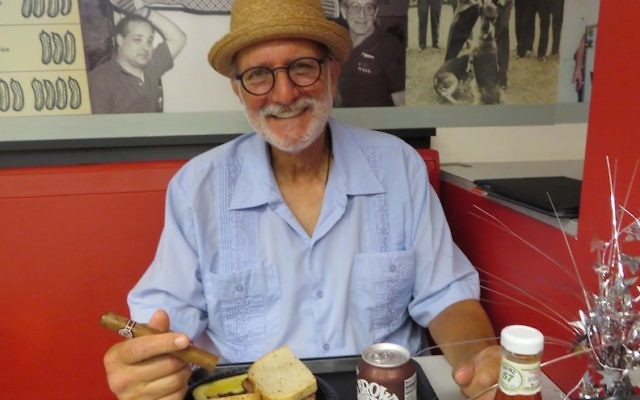 Alan Gross with some of his favorite things — a pastrami sandwich and a Cuban cigar — at Loeb's Deli in Washington DC, July 12, 2017. (Ron Kampeas)