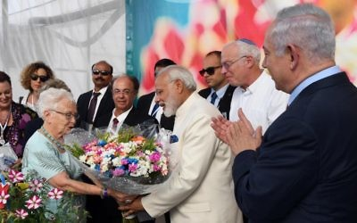 Indian Prime Minister Narendra Modi, center in white, is given a bouquet of flowers during a visit to the Danzinger Flower Farm accompanied by Prime Minister Benjamin Netanyahu, far right, on July 4, 2017. (Haim Tzach/GPO)
