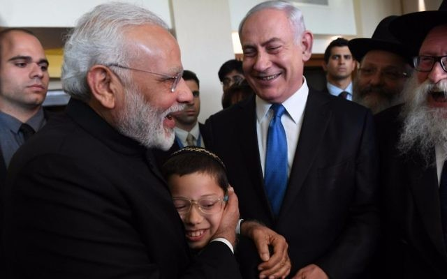 Indian Prime Minister Narendra Modi, left front, embraces 11-year-old Moshe Holtzberg, son of murdered Chabad emissaries Rabbi Gavriel and Rivkah Holtzberg, who were killed in a November 2008 terror attack in Mumbai, in Tel Aviv on July 5, 2017. Prime Minister Benjamin Netanyahu is in a blue tie. (Haim Tzach/GPO)